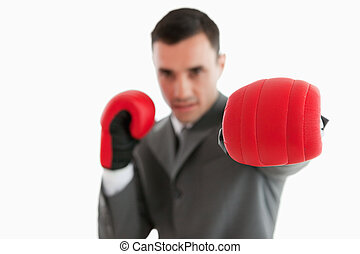 Close up of boxing glove being used by businessman
