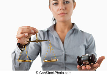 Scale and gavel being held by female lawyer against a white...