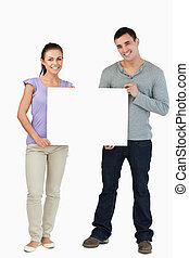 Young couple holding sign
