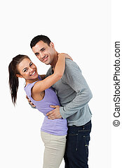 Young couple hugging each other against a white background