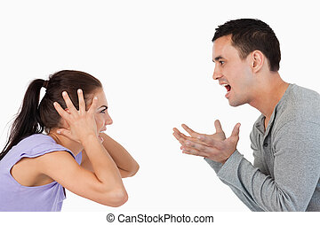 Young couple yelling at each other against a white...