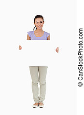 Young female holding sign against a white background