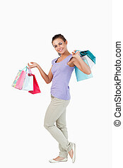 Side view of smiling young female with shopping bags