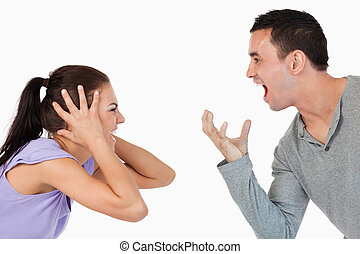 Young couple shouting at each other against a white...