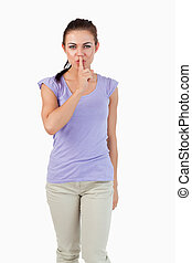 Young female asking for silence against a white background
