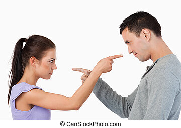 Young couple pointing at each other against a white...