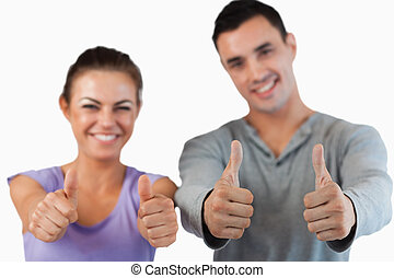 Thumbs up being given by young couple - Thumbs up being...