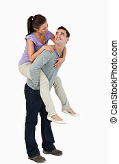 Young female carried piggyback by her boyfriend