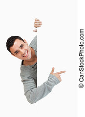 Smiling young male pointing around the corner against a...