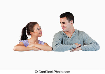 Young couple looking at each other while leaning on a wall...