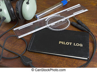pilot log on a wooden table with headset, fuel tester and...