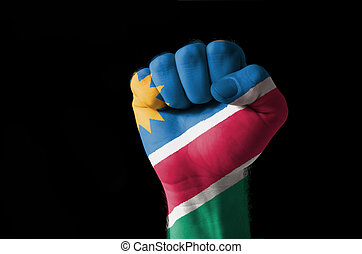 Fist painted in colors of namibia flag - Low key picture of...
