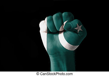 Fist painted in colors of pakistan flag - Low key picture of...