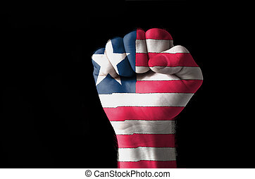 Fist painted in colors of liberia flag - Low key picture of...