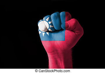 Fist painted in colors of taiwan flag - Low key picture of a...