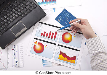 hand specifies the financial chart, a workplace - The hand...