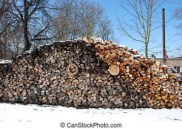 Firewood pile next to boiler house. - Snow covered firewood...
