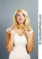 Hopeful woman crossing fingers - Blonde caucasian woman...