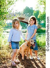 kid girls with Golden retriever puppy outdoor