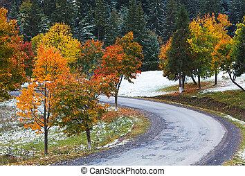 First winter snow and autumn colorful foliage near mountain secondary road (Carpathian, Ukraine)