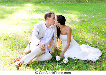 couple happy in love kissing sitting in park