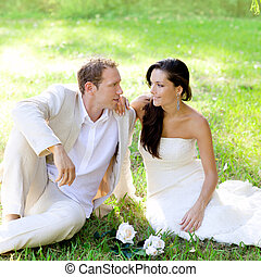 couple just married sitting in park grass