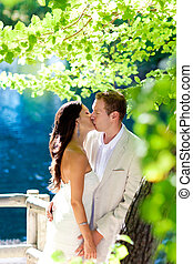 couple in love kissing in forest tree blue lake outdoors