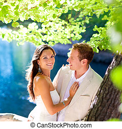 couple in love hug in forest tree blue lake
