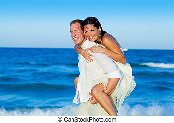couple in love piggyback playing in beach - couple in love...