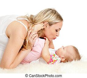 Loving mother kisses her child;  child is lying on sheepskin