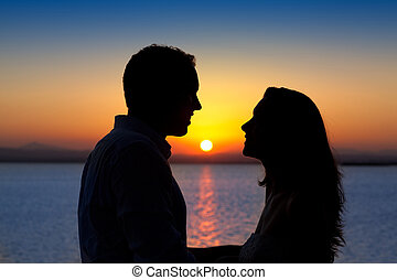 couple in love back light silhouette at lake sunset