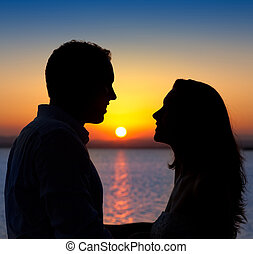 couple in love back light silhouette at lake sunset - couple...