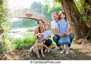 family in nature outdoor with dog father mother and...