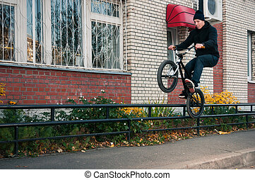 Biker doing icepick grind trick on low, black rail