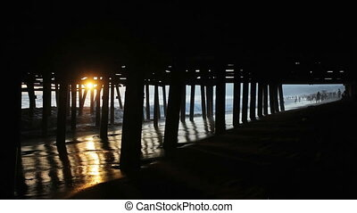 Sun Under the Pier - Sunlight shining through the pylons of...
