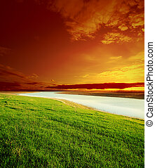 red sky on sunset over river and green grass
