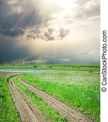 rural road in green grass under dramatic sky