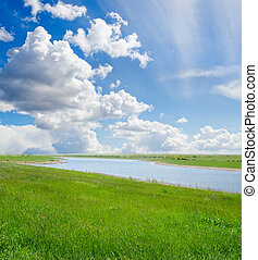 green grass and cloudy sky with river