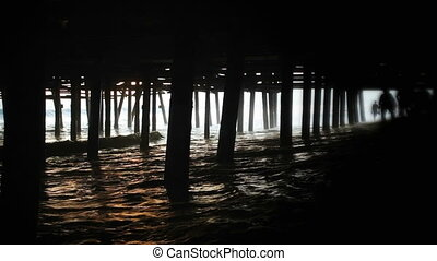 Santa Monica Pier - A couple, in silhouette, running through...