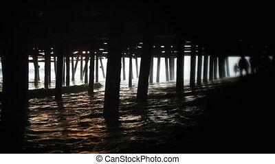 Santa Monica Pier - A couple, in silhouette, running through...