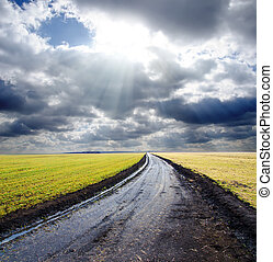 wet rural road under dramatic cloudy sky with sunbeams