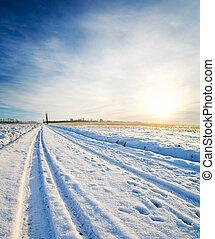 rural road under snow. winter sunset
