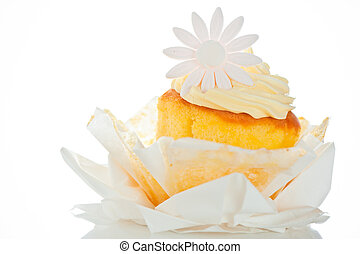 Cupcake with vanilla cream and sugar flower on a white...