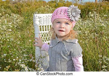 Little girl on wicker chair