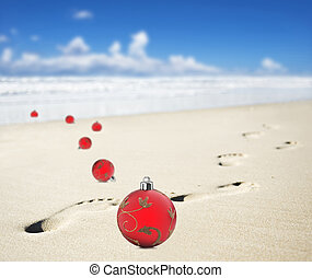 Christmas baubles on a beach with footprints