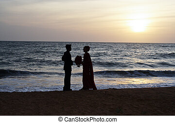 married couple stands happy at the beach in sunset - married...