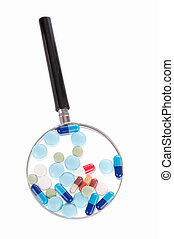Pills on magnifying glass - Group of different pills on...