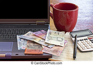 Global Currency - Laptop computer with money from different...