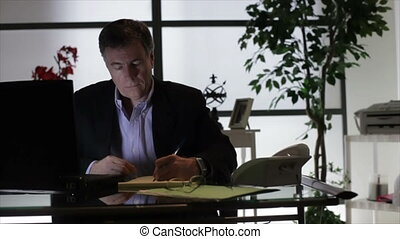 Businessman Working Late - A businessman sitting in his...