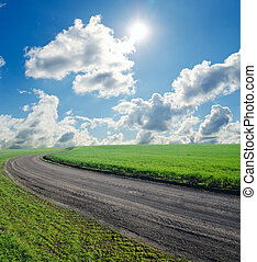 summer landscape with rural road, green field and blue cloudy sky with sun